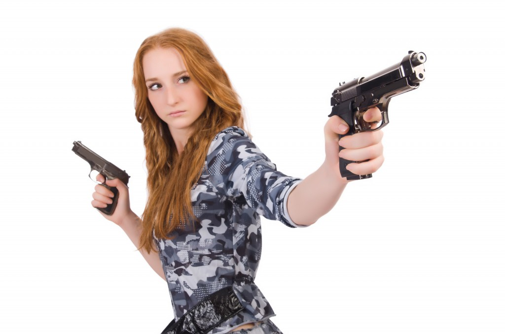 Young woman soldier with gun on white